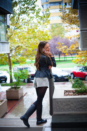 autmn: smiling beautiful  young woman speaking on smartphone wearing black jacket, shorts and black rubber boots, outdoor shot, rainy autmn day in the city