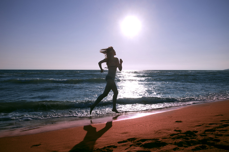 blue sea: woman running on the sand at beach at sunset, full body shot, side view