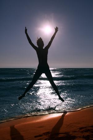 full shot: woman silhouette jump to the sun on sandy  beach, full body shot,  silhouette
