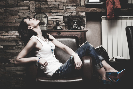 Caucasian woman: woman in blue jeans and white t-shirt sit in leather armchair in room , full body shot indoor, side view