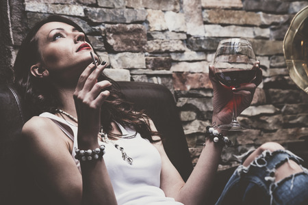 woman with glass of red wine and cigarette, wearing blue jeans and white t-shirt,   on leather couch, indoor shot