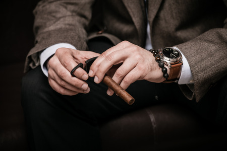 photo of accessories: elegant man wearing suit and white shirt cut Cuban cigar indoor shot, closeup, selective focus Stock Photo