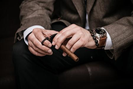 hombre fumando: hombre elegante vistiendo traje y camisa blanca corta tiro de interior puro cubano, primer plano, atención selectiva Foto de archivo