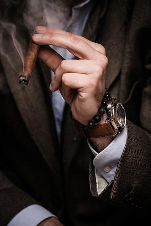 indoor shot: elegant man wearing suit and white shirt smoking  cigar indoor shot, closeup, selective focus
