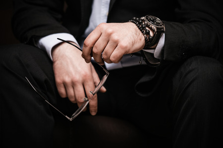 man in suite: elegant man in black suite and white shirt hold eyeglasses in hand wearing watch and bracelet indoor shot selective focus closeup