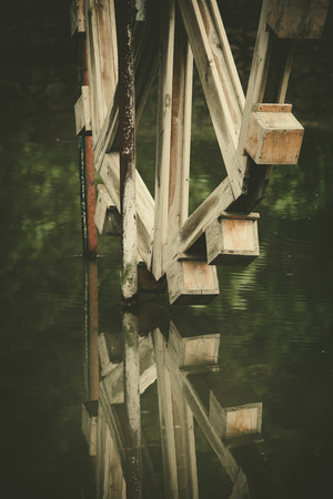 watermill: old wooden  watermill and a reflection in water closeup