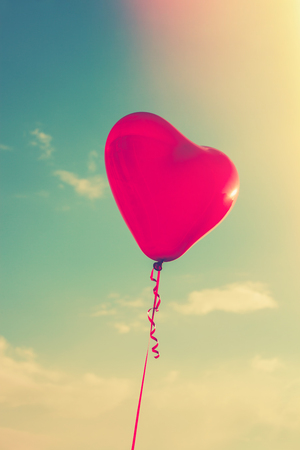 pink skies: beautiful red heart shape balloon against sky with clouds, retro colors, sun flare