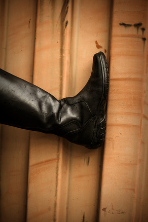 rubber sole: female leg in black  leather high boots on grunge orange background, outdoor shot