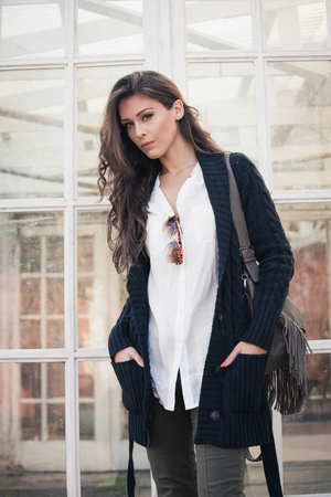 winter trendy fashion young woman in dark blue cardigan, white shirt and green pants, stand in front glass doors