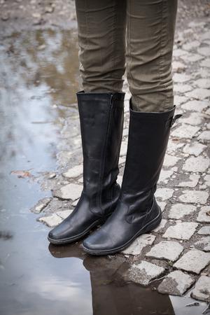 botas de lluvia: piernas femeninas en botas de cuero negro sobre cantos rodados en el borde del charco de la lluvia, de cerca