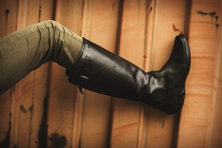 rubber sole: female leg in green pants and black  leather high boots on grunge orange background, outdoor shot, closeup