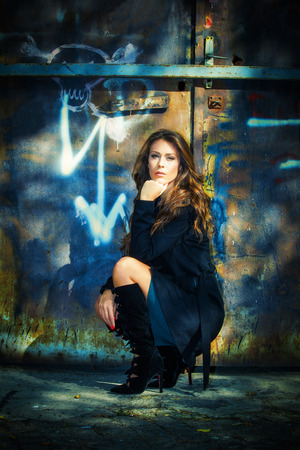full metal jacket: beautiful long hair young woman portrait in coat and high heels black boots in front old rusty metal doors, full body shot
