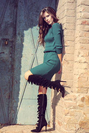 beautiful young woman in short dress and high heels boots against brick wall and old metal door, retro colors, full body shot