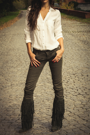 tassel: woman in white shirt,  green tight pants and tassel boots, stand on cobble