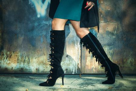 woman legs in black high heel boots  and short skirt outdoor shot against old metal door Stock Photo