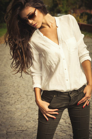 casual fashion: beautiful long hair young woman portrait wearing white shirt and sunglasses outdor shot sunny autumn day Stock Photo