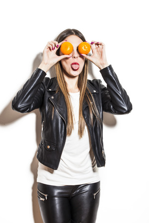 young woman with tangerines on her eyes making fun, wearing black leather jacket and leggings