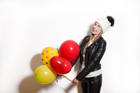 black pants: smiling young woman wearing black leather jacket, pants and white wool cap, hold balloons
