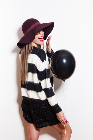 black hat: young woman with hat sunglasses and sweater laughing and hold black balloon