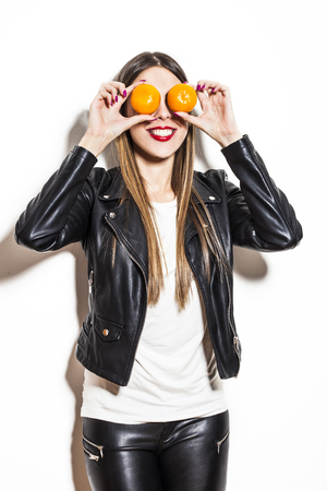clowning: smiling young woman with tangerines on her eyes making fun, wearing black leather jacket and leggings Stock Photo