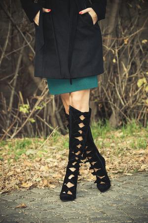 3744668292  47346313 - Mujer de la manera en abrigo oscuro y negro otoño los altos  talones de las botas en adoquín con las hojas caídas