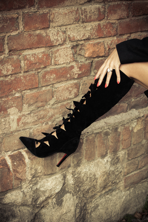 velours: female foot in black  autumn high heels boots on brick wall outdoor shot, closeup Stock Photo