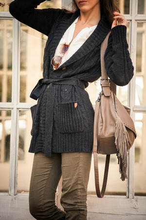winter fashion: woman in worm dark wool sweater,  black leather high boots hold leather hand bag with tassels   stand in front glass door, closeup, outdoor shot Stock Photo