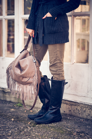 hand hold: woman in worm dark wool sweater,  black leather high boots hold leather hand bag with tassels   stand in front glass door, closeup, outdoor shot Stock Photo