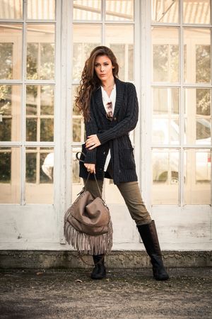 leather pants: woman in worm dark wool sweater,  black leather high boots hold leather hand bag with tassels stand in front glass door, full body shot