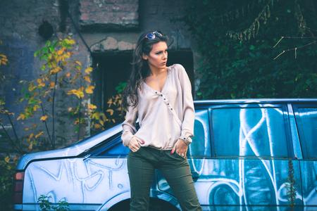 long pants: young beautiful long hair woman portrait with sunglasses , outdoor in the city, wearing shirt and pants in front of old car Stock Photo