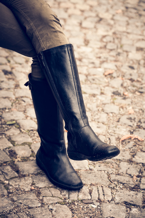 women legs: woman legs in black  autumn high heels boots on cobble, selective focus Stock Photo