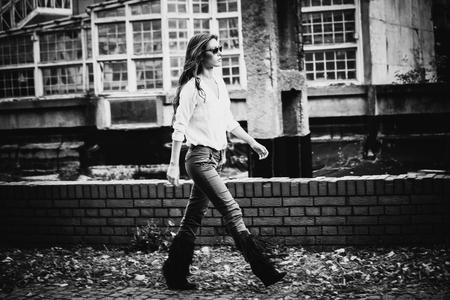 mujeres fashion: Mujer joven en camisa, pantalones ajustados y botas de borla, caminar delante del edificio viejo, blanco y negro, foto de cuerpo entero, pequeña cantidad de grano añadido