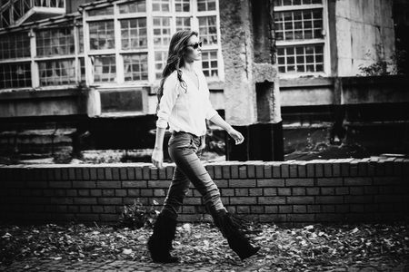 on the move: young woman in shirt,  tight pants and tassel boots, walk in front of old building, black and white, full body shot, small amount of grain added