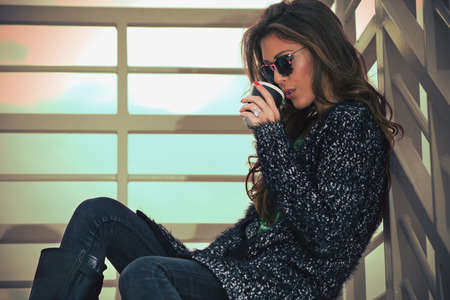 drink coffee: young woman in cardigan and sunglasses drink coffee from paper cup on stairs, autumn day outdoor Stock Photo
