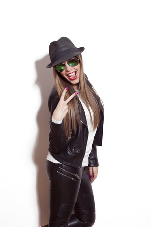 making faces: young blonde woman making faces and gestures, wearing sunglasses hat black leather jacket and leggings Stock Photo