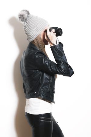 camera girl: girl take photo with digital camera, wearing wool cap, leather jacket and black leggings Stock Photo