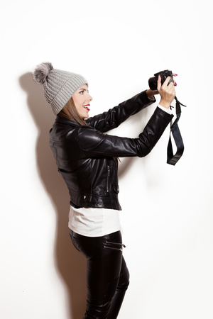 camera girl: girl take selfie with digital camera, wearing wool cap, leather jacket and black leggings