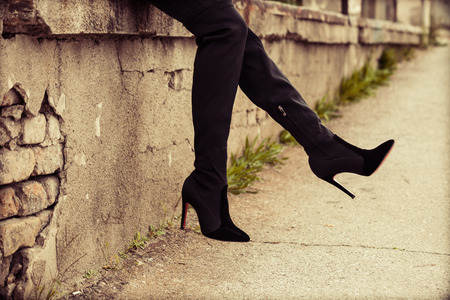 Legs and heels: young woman in  high heels boots,  outdoor on street, closeup