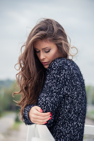 long hair brunette: pensive beautiful young long hair woman in cardigan, outdoor autumn day portrait
