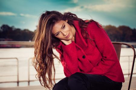 ojos verdes: moda joven sentarse en el café al aire libre por el río desgasta la capa roja, día de otoño