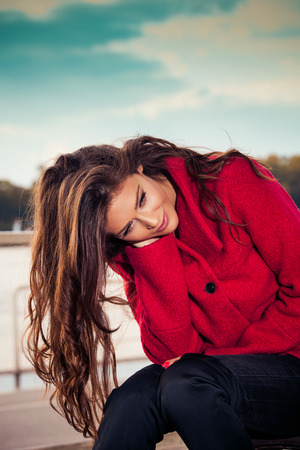 stylish hair: fashionable young woman sit at outdoor cafe by the river  wearing red coat, autumn day Stock Photo