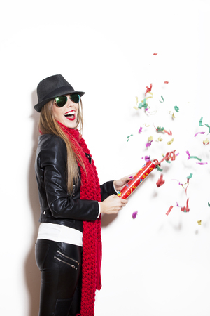 red scarf: girl in leather jacket, hat, red scarf and sunglasses make fun with confetti, studio white Stock Photo