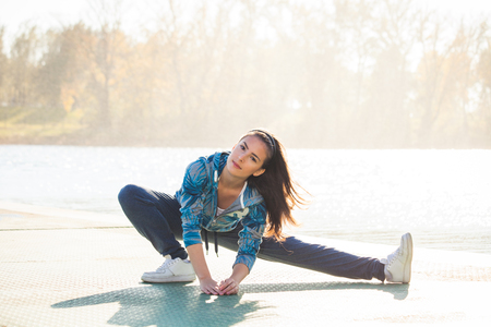 tracksuit: young woman in tracksuit exercise on pontoon at lake,  sunny autumn day, full body shot,
