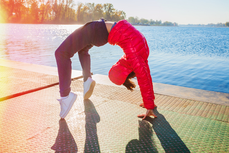 full strenght: young woman in tracksuit and red jacket exercise on pontoon at lake,  sunny autumn day, full body shot