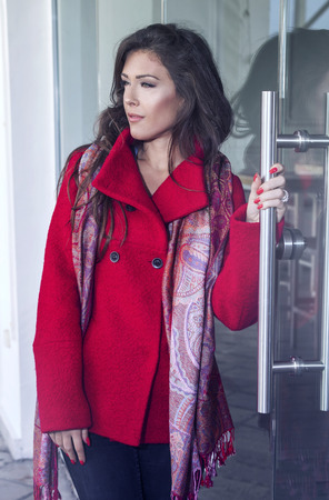 glass door: fashionable young woman  wearing red coat and cashmere scarf stand in front glass door, outdoor in the city, autumn day Stock Photo