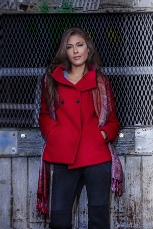 brunette woman: fashionable young woman  wearing red coat and cashmere scarf stand in front old grid door, outdoor in the city