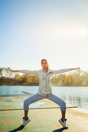 tracksuit: young woman in tracksuit exercise on pontoon at lake,  sunny autumn day, full body shot, balance