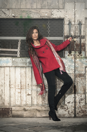 casual woman: fashionable young woman  wearing red coat, black pants, high heel shoes and cashmere scarf stand in front old grid door, outdoor in the city, full body shot Stock Photo