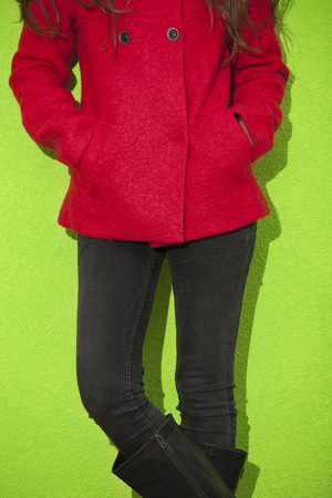 black pants: young woman in red coat and black pants lean on green wall, outdoor shot