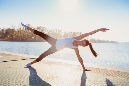 undershirt: young woman in leggings and white undershirt   on pontoon at lake practice yoga, sunny autumn day, water droplets all around from near by water fountain